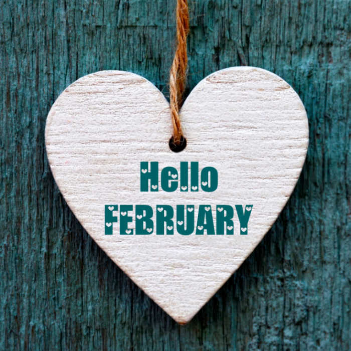 "Wooden heart on a sting in front of blue wool with words ""Hello February."""