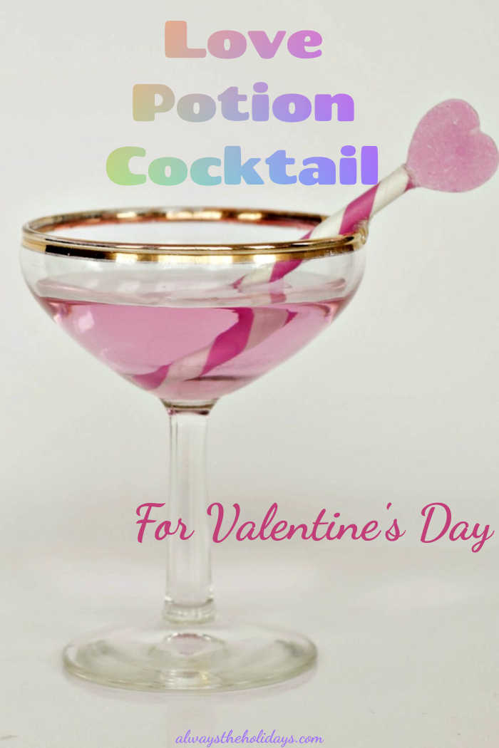 "Pink drink with heart garnish in a martini glass and words ""Love Potion Cocktail for Valentine's Day."""