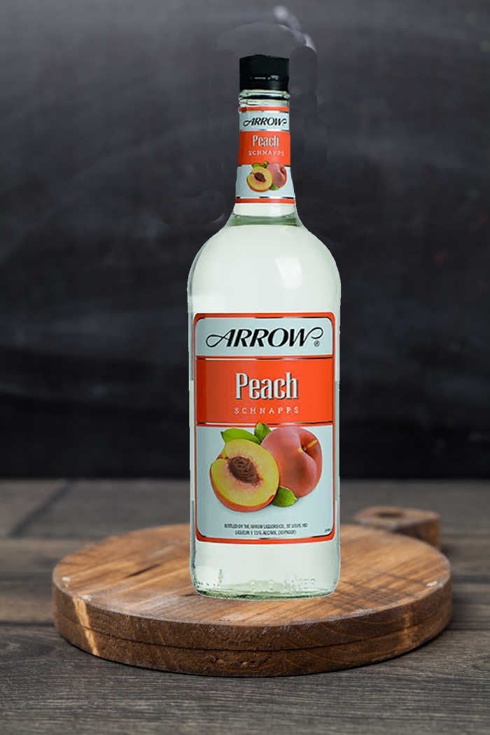 Bottle of peach schnapps on a wooden cutting board.