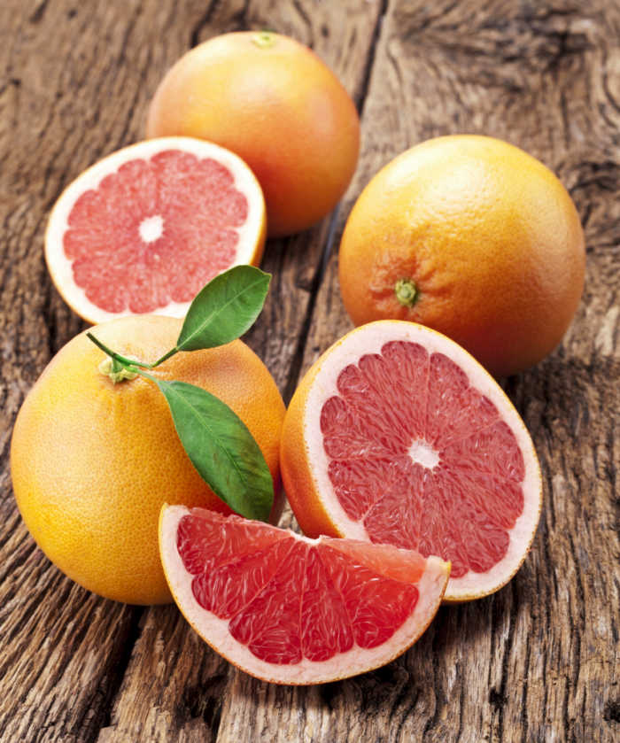 pink grapefruit, whole and cut.