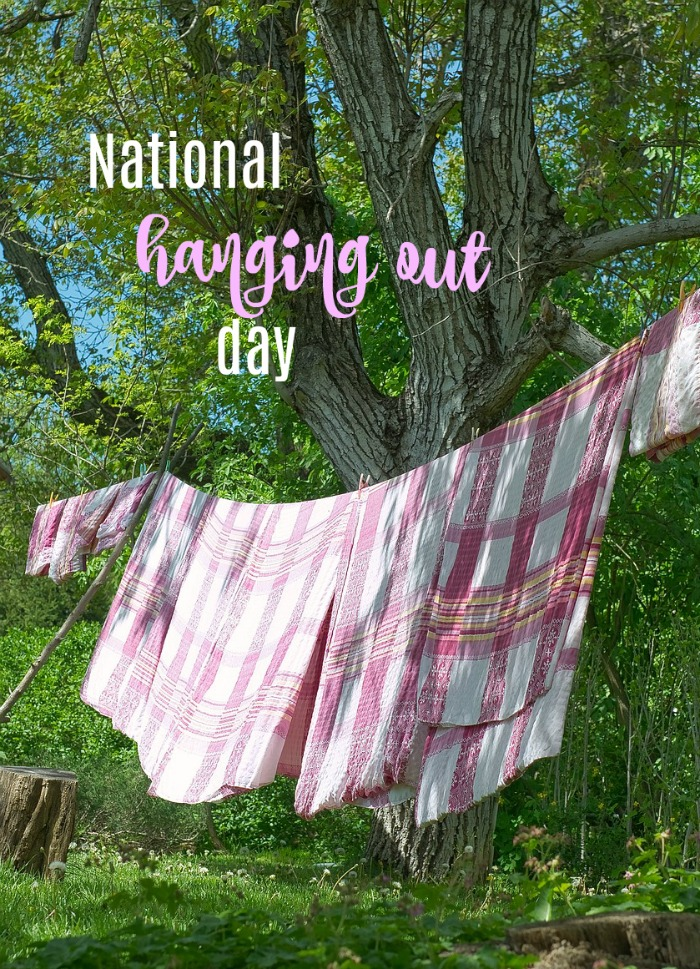 """A tree with a clothesline holding red and white checked towels with a text overlay that reads """"National Hanging Out Day""""."""