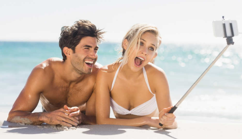 Man and woman on the beach in the water taking a selfie.