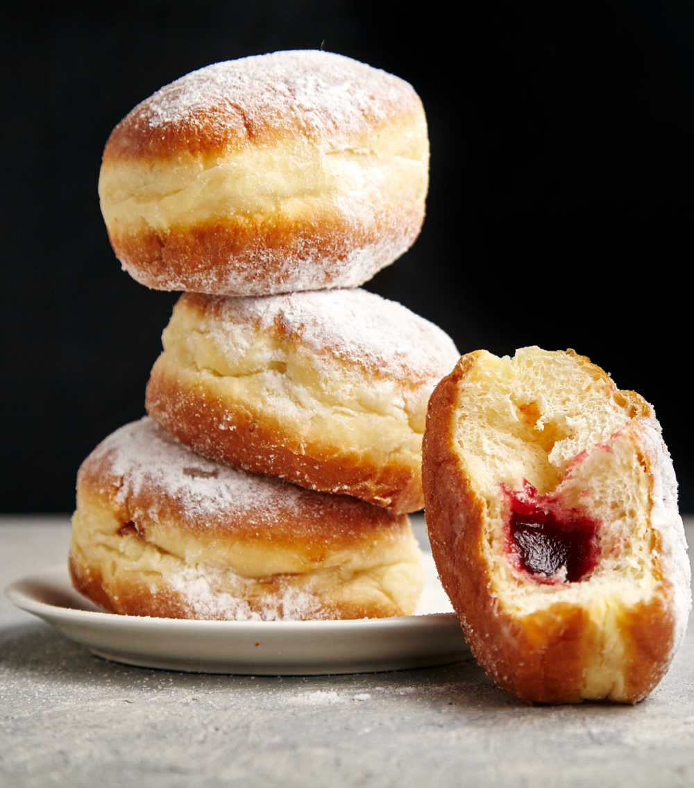 stack of jelly filled donuts on a plate.