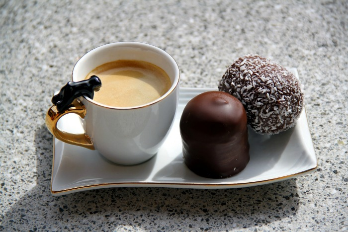 Coffee with a coconut ball and a chocolate
