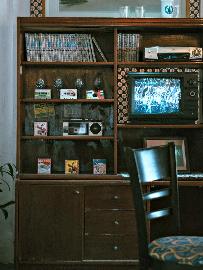 Color TV in a book case with memorabilia