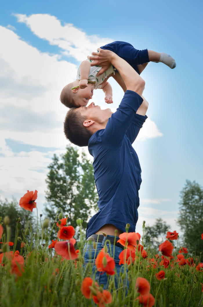loving father and son in a field of flowers reminds us about be a kid again day