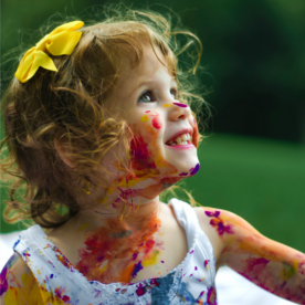 Little girl with paint on her face and clothes