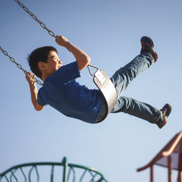 Boy swinging at a playground