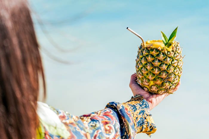 woman holding a pina colada in a pineapple at the beach