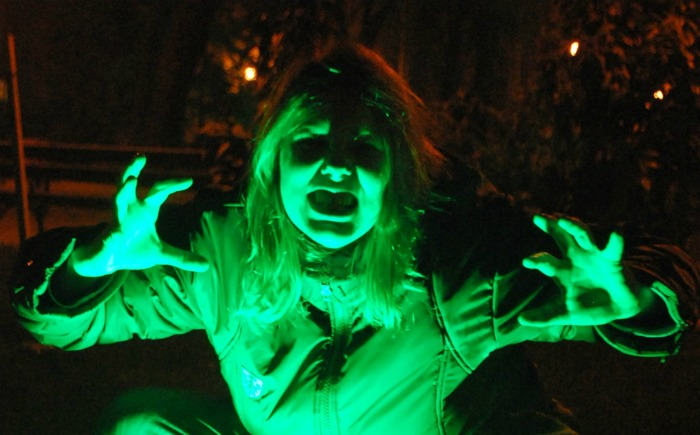 woman zombie costume under a neon light