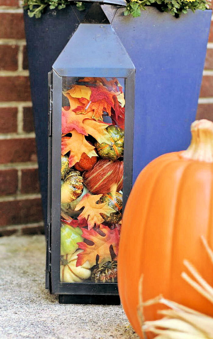 DIY fall decor ideas - Lantern filled with pumpkins and leaves