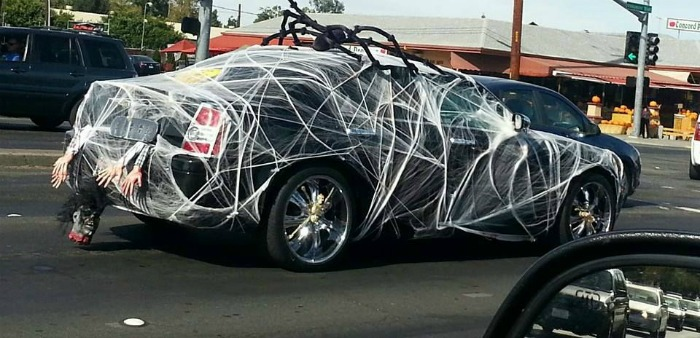 Car covered in spider webs and a giant spider.