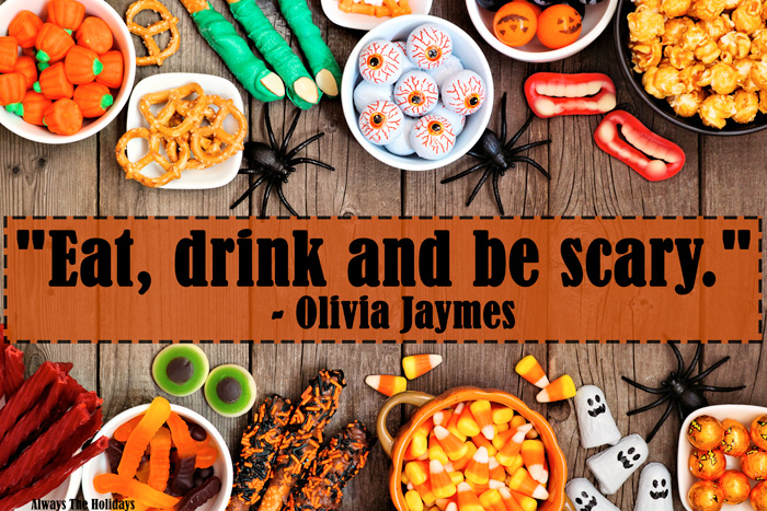 "A table with bowls of Halloween candy and a Halloween qoutes over it reading ""Eat, drink and be scary.""."