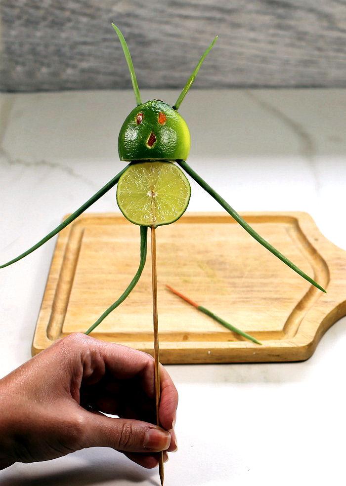 hand holding a lime devil garnish near a cutting board.