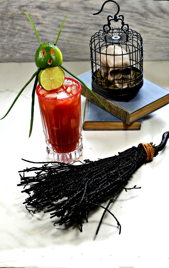 Witches broom and skull near a glass of bloody Mary with a lime devil garnish.