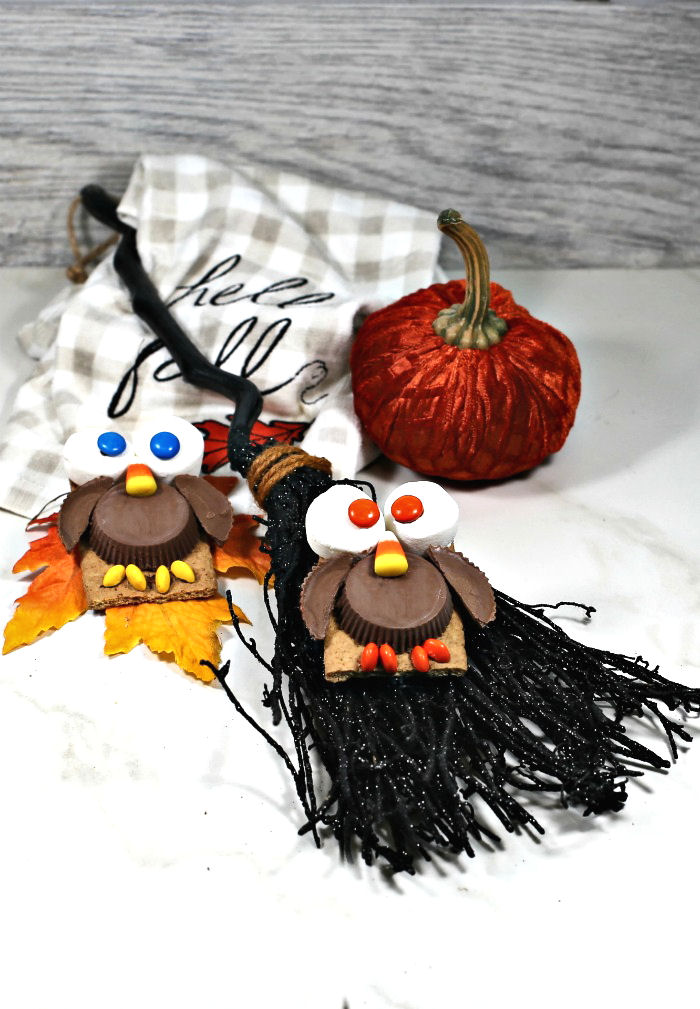 Halloween owl cookies on a broomstick with a pumpkin.
