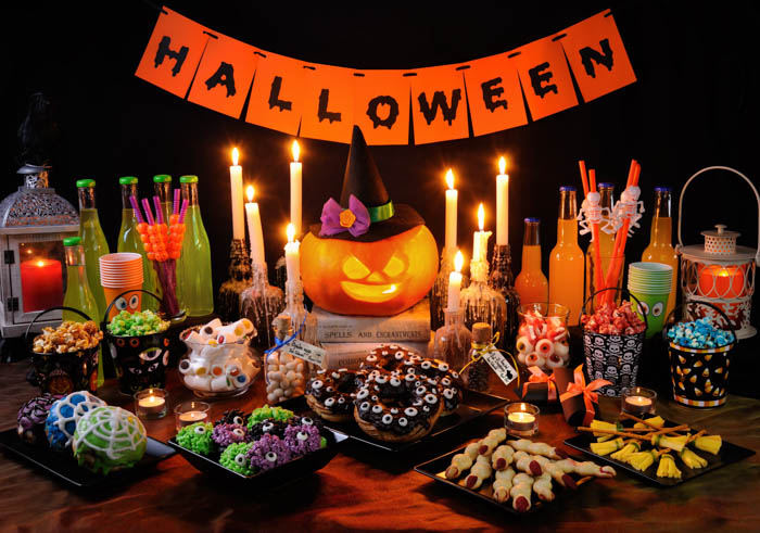 "A Halloween buffet table with food, drinks, candles, a pumpkin and a banner that says ""Halloween""."