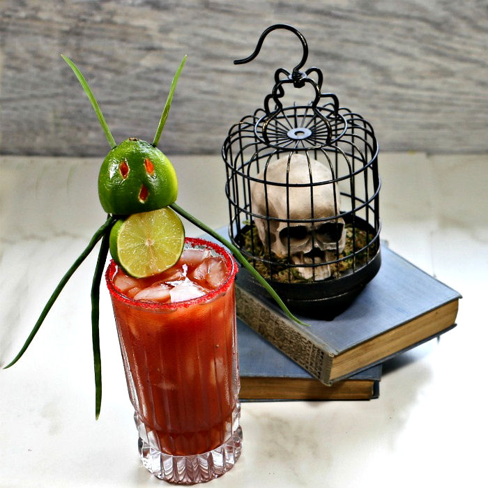 Halloween bloody Mary with a devil garnish and skull on books.