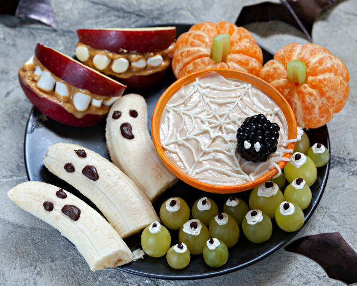 Healthy Halloween snack plate with orange pumpkins, banana ghosts, grape eyeballs and mouth apples.