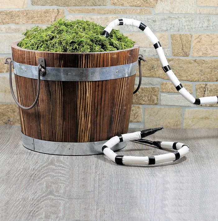 Bucket filled with moss and Beetlejuice snakes trying to climb in.