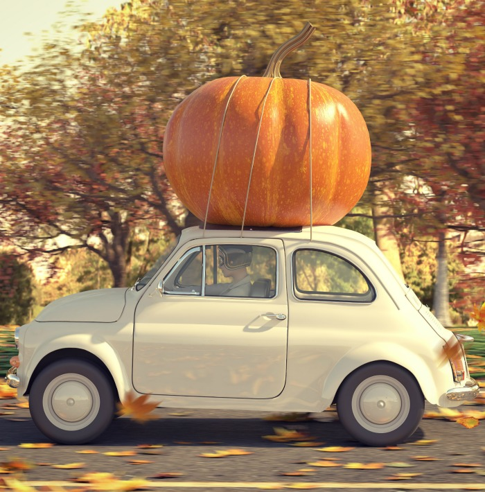 Halloween car decorations: Small beige care with a large pumpkin.