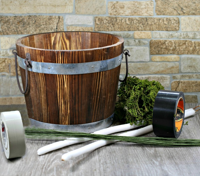 Wood bucket, moss, glue, tape, striped fabric and foam dowels.