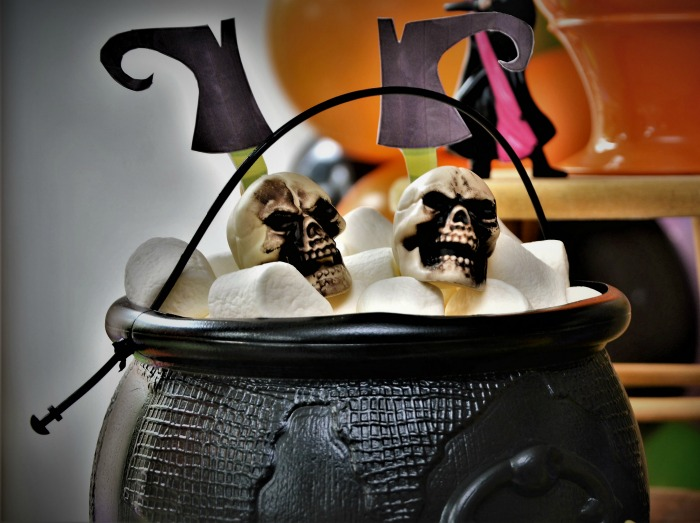 Marshmallows in a black cauldron with witch feet and skulls.