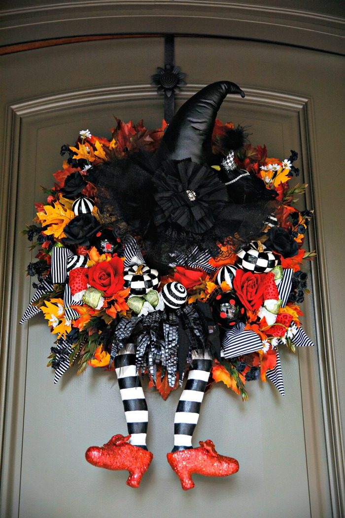 Witch legs door wreath with ruby slippers.
