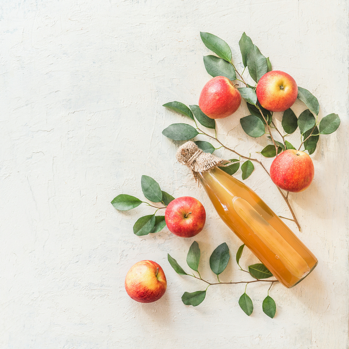 A bottle of apple cider surrounded by apples and apple branches.