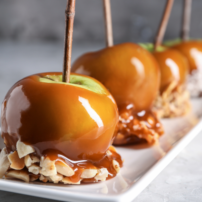 A plate of homemade caramel apples with an almond topping.