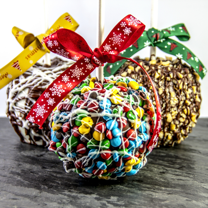 Three caramel apple toppings with bows tied on the sticks and different candy on them including m&ms.