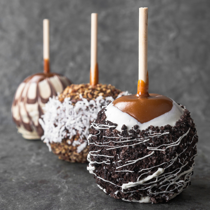 Three caramel apples with different toppings such as oreo crumbles, white chocolate, coconut, milk chocolate and nuts.
