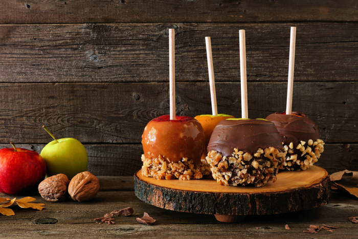 A wooden display platter holding caramel apples and chocolate caramel apples with peanut toppings and chocolate toppings.