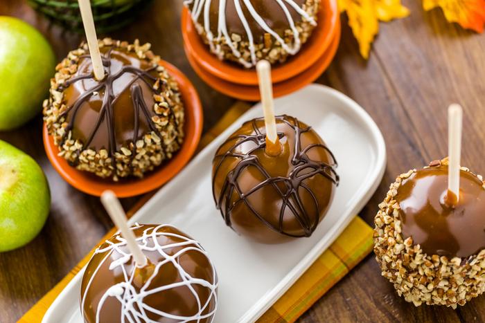 An assortment of dark chocolate caramel apples and white chocolate caramel apples, some with peanuts.