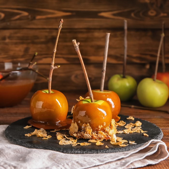 Three breakfast inspired caramel apples with cornflake toppings.