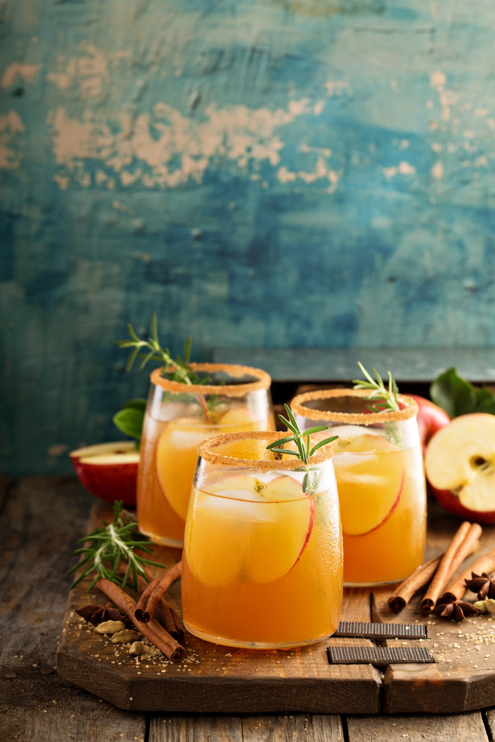 Three apple cider cocktails with apples and rosemary garnishes for apple cider day.