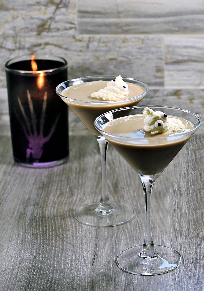 Two Ghostbuster cocktails with whipped cream ghosts and a black candle.