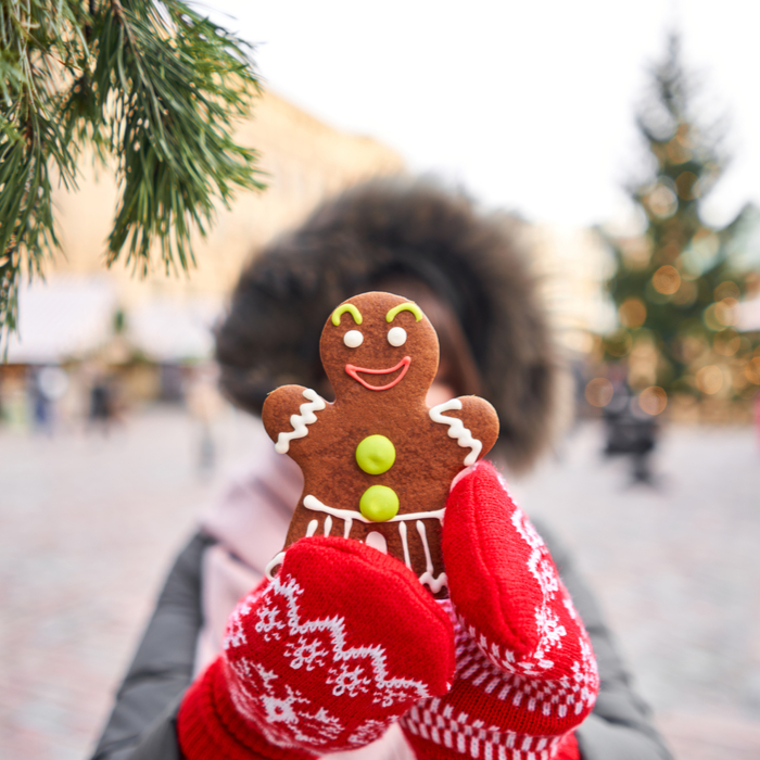 A woman holding up a gingerbread cookie in front of her face at a Christmas market.