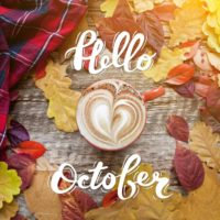 Leaves, cup of coffee and plaid shirt with words Hello October.
