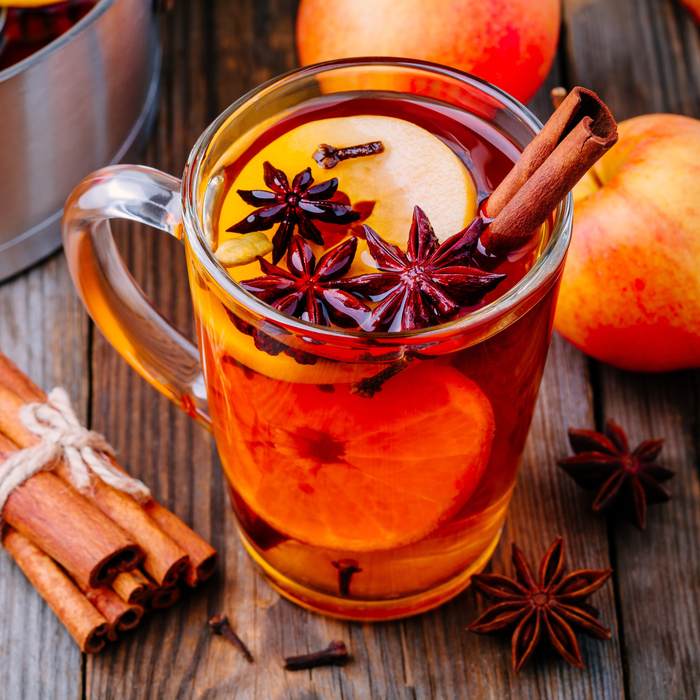 Hot spiced apple cider in a glass mug on a wooden table surrounded by cinnamon sticks, star anise, oranges and apples.