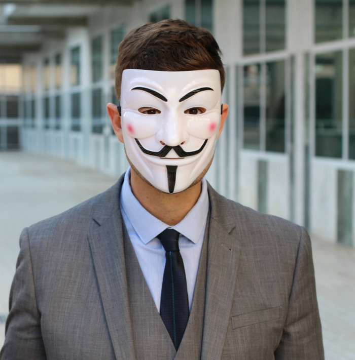 Man wearing a white Guy Fawkes mask.