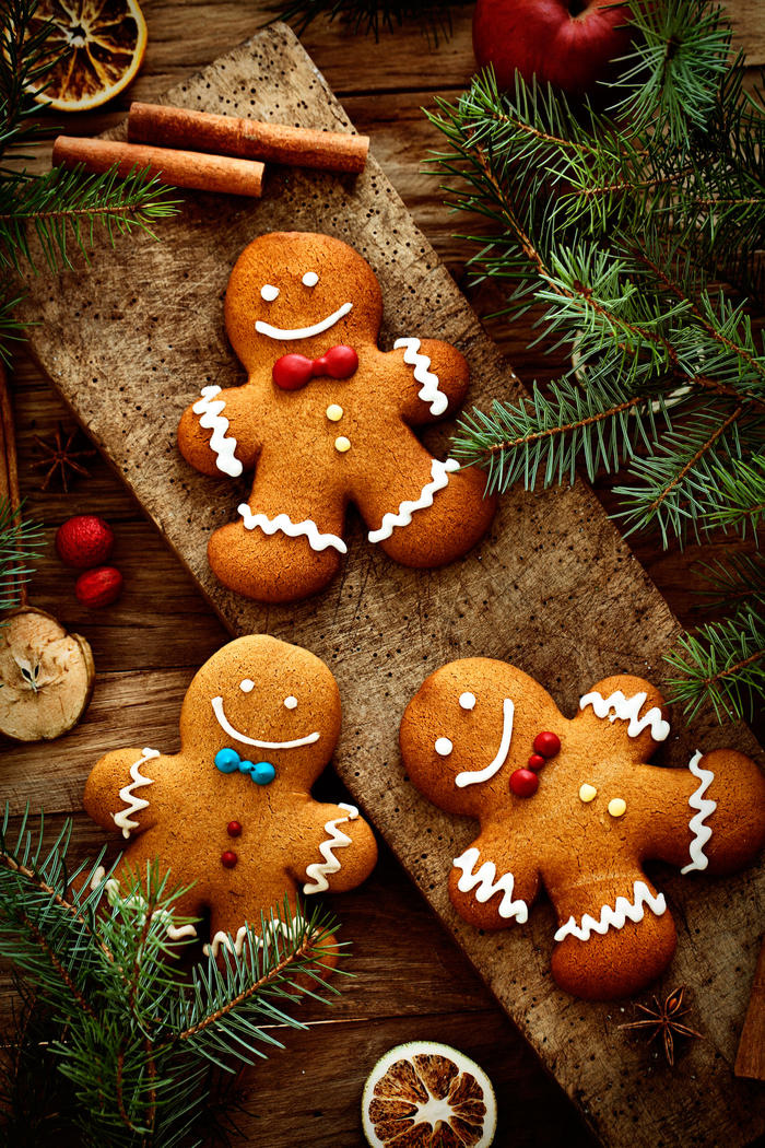 Three gingerbread cookies arranged on a table with fir branches and cinnamon sticks.