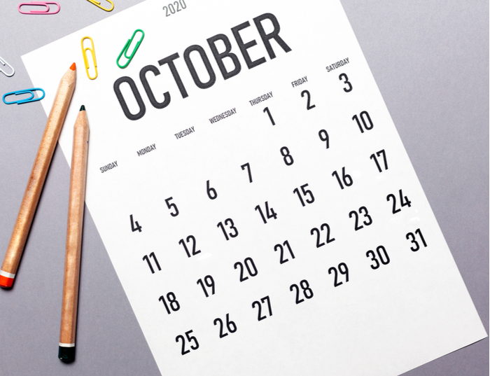 An October calendar with paperclips and pencils surrounding it.