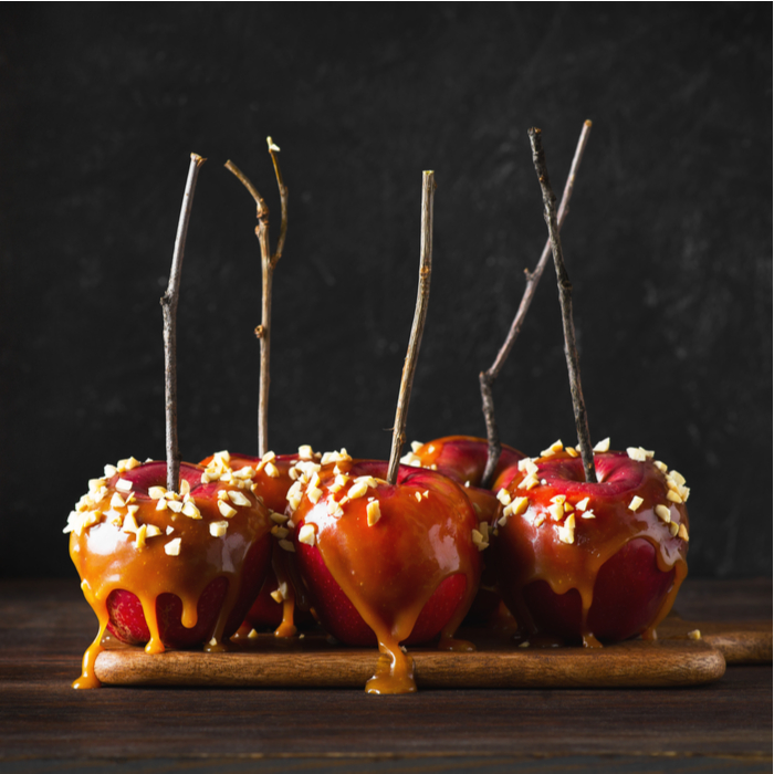 A plate of rustic caramel apple with twigs for sticks and peanut toppings.