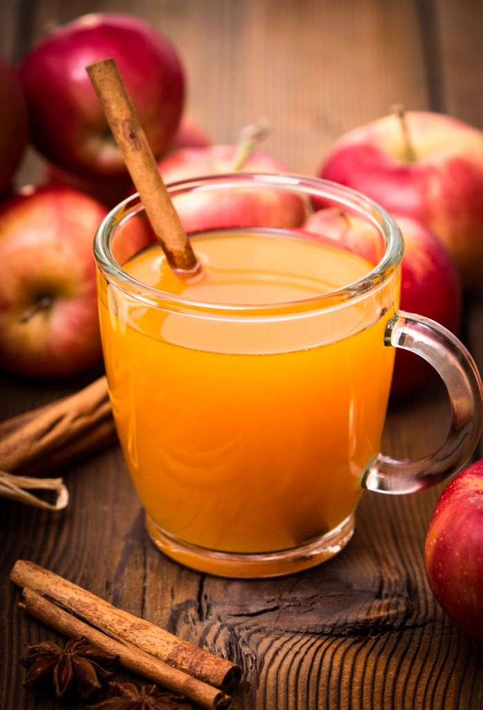 A glass of hot apple cider garnished with a cinnamon stick next to fresh apples on a wooden table.