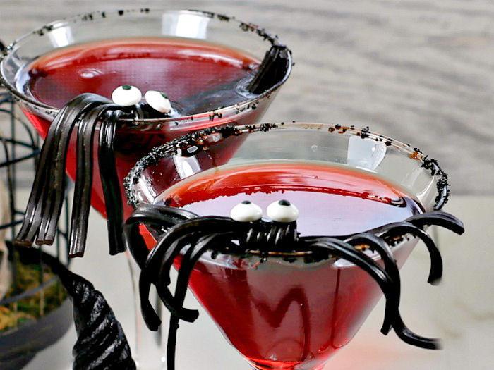 Spider garnish in a vampire cocktail with black rim.