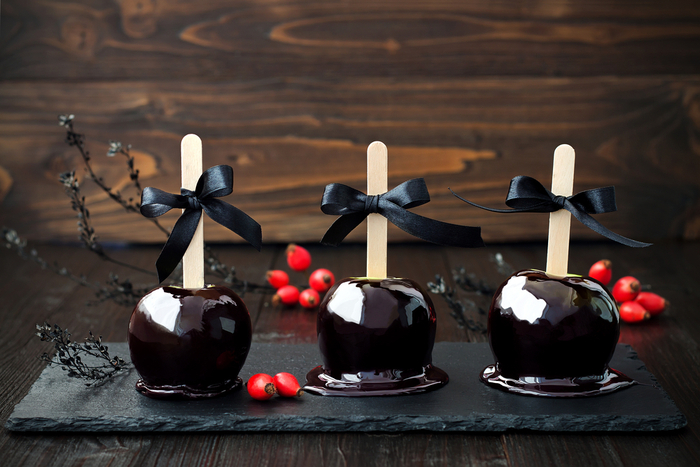 Three black spooky caramel apples with bows on a slate serving platter.