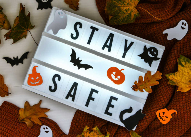White fence and Halloween figures with words stay safe.