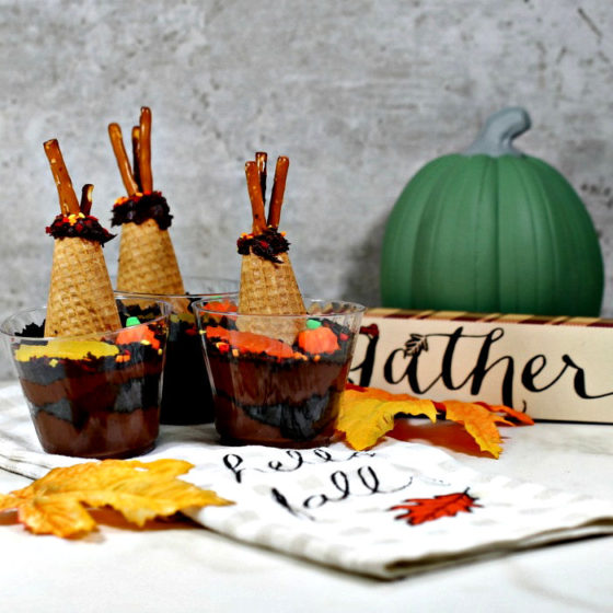 Dirt recipe chocolate pudding shaped like teepees, with sign towel, leaves and pumpkin.