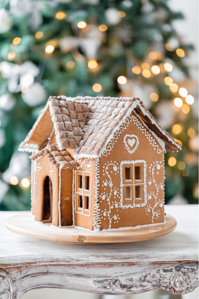 A simply decorated gingerbread house on a wooden table against a Christmas tree backdrop.